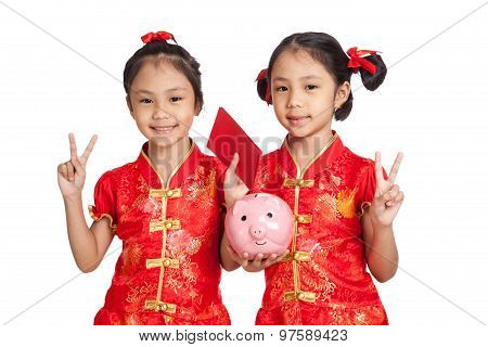 Asian Twins Girls In  Chinese Cheongsam Dress With Coin Bank And Red Envelopes