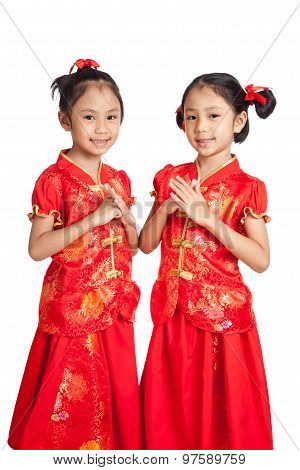 Asian Twins Girls In  Chinese Cheongsam Dress With Gesture Of Congratulation
