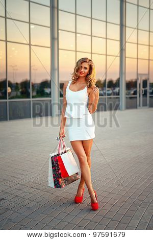 Portrait of a beautiful blond girl with shopping bags