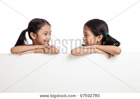 Happy Asian Twins Girls  Behind White Blank Banner