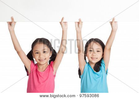 Happy Asian Twins Girls With White Blank Banner Over Head