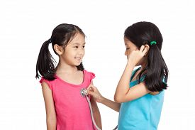 pic of identical twin girls  - Happy Asian twins girls with stethoscope isolated on white background  - JPG