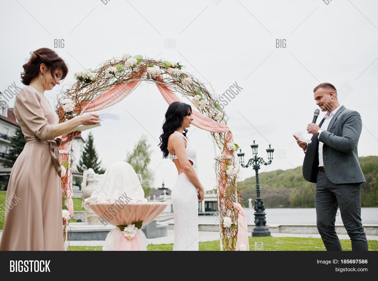 Young Fashionable Lovely Couple With Speech Master Of Wedding Ceremony Against Decor Arch On