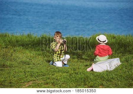 boy taking pictures of his sister on the seafront