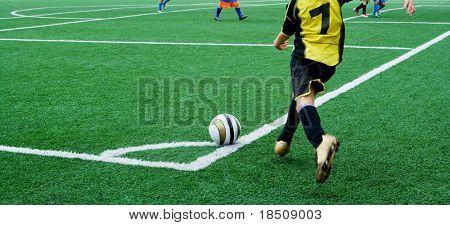Young soccer player in a corner kick