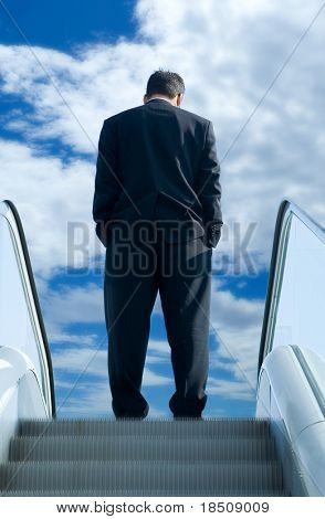 Business man on the escalator