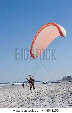Paraglider prepares for takeoff on the beach