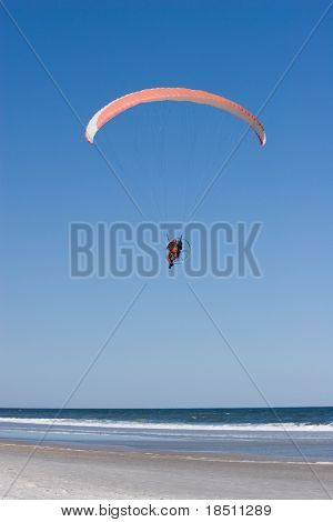 Paraglider flying over the beach with a paramotor