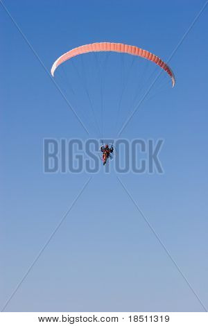 A Paraglider flies in the blue sky