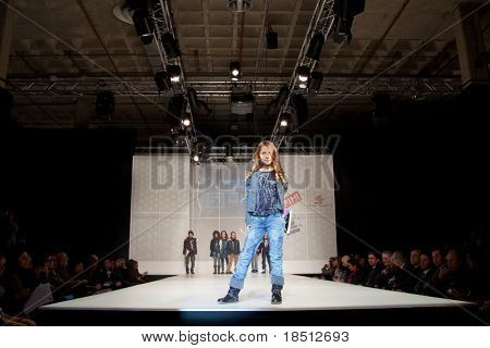 VALENCIA, SPAIN - JANUARY 21: An unidentified child model at the FIMI Children's Winter Fashion Show with the designer Tumble Dry in the Feria Valencia on January 21, 2011 in Valencia, Spain.