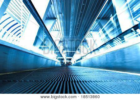 Escalera mecánica en movimiento en la perspectiva de la sala de oficina