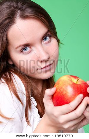 portrait of the beauty girl with red color apple in park