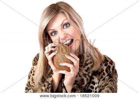 A menina com um casaco de peles roendo coco
