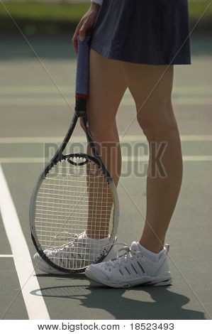 Female tennis player's legs and racket