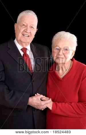 handsome elderly couple, formal portrait over black