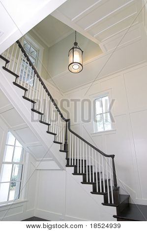 curved staircase in expensive home with white woodwork