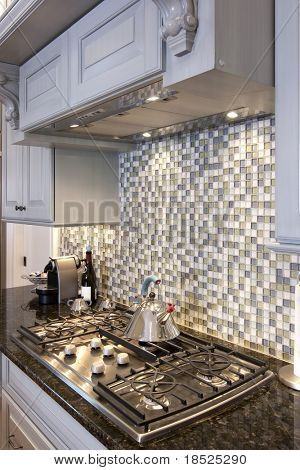 beautiful kitchen stove and backsplash made from glass tile