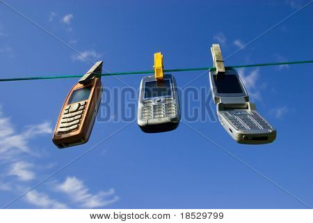 Three Cell Phones Drying on Clothesline / Network of wireless devices