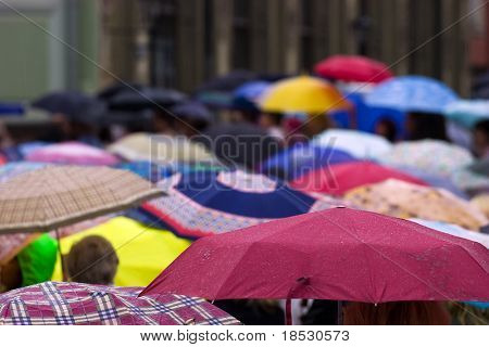 Busy street with crowd of people with umbrellas