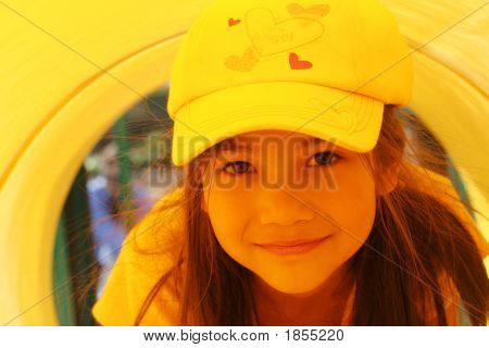 Spunky Little Girl Playing Inside Yellow Tube