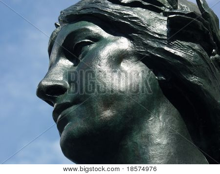 Statue of a goddess against a clear blue sky, in Montreal, Quebec, Canada.