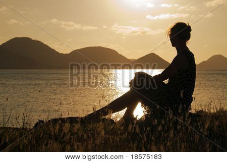 A woman watching the sunset in the Caribbean.