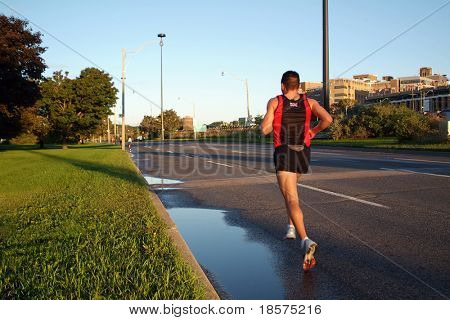 A solitary marathon runner sets the pace during the opening stages of a race.