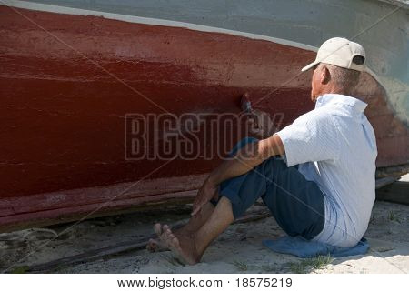 A man slowly painting the hull of an old boat.