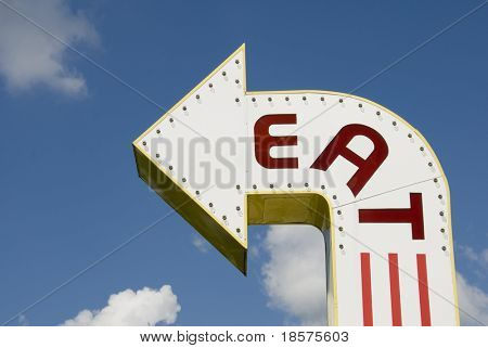 A three-dimensional metal EAT sign in a sans-serif typeface.