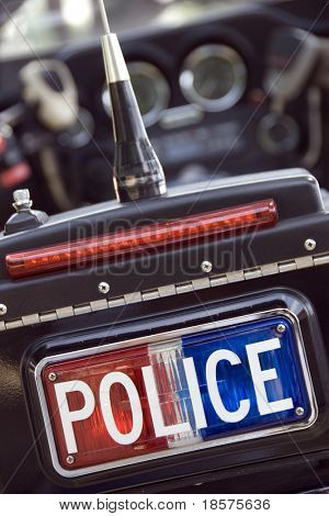 A red white and blue police sign on the back of a motorcycle.