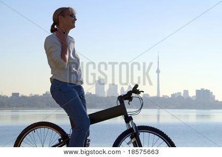 A woman sitting on a mountain bike near Lake Ontario, with the Toronto skyline in the background.