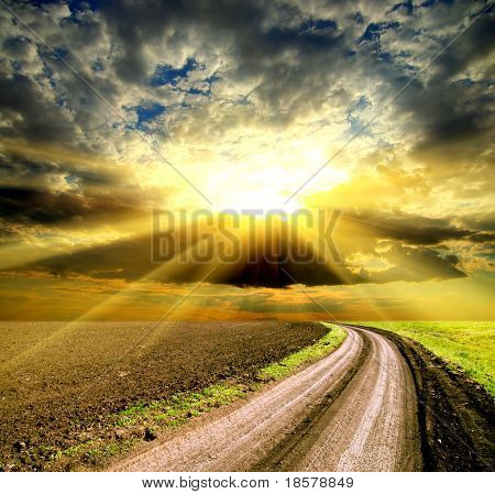 sun and clouds over field with road