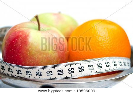 Two apples and orange wrapped with centimeter tape (centimeter tape show number 60, ideal for waist)