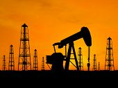 picture of rig  - Oil rig silhouettes over orange sky  - JPG