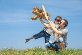 Father And Son Playing With Cardboard Toy Airplane In The Park At The Day Time. poster