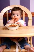 image of finger-licking  - Adorable baby eating spaghetti in her high chair - JPG
