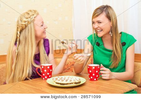 Meninas apreciando chá e bolo