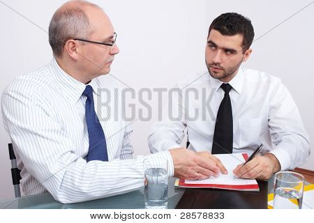 Two businessman, one mature and one young sitting at table during meeting