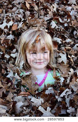 Young Girl Smiling in Leaf Pile