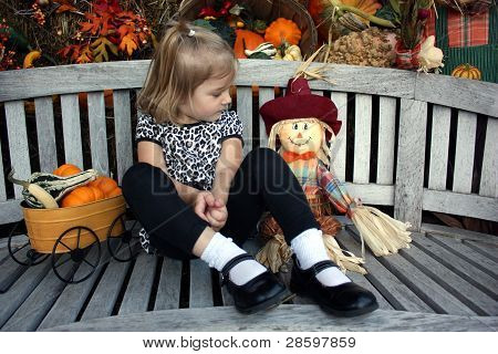 A young girl making friends with a small scarecrow
