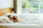 Woman sleeping on bed in luxury hotel room in the morning infront of big window. Chilling well on co poster