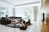 Two teenagers watching tv while relaxing on couch in living room poster