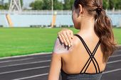 Young Female Runner Standing And Putting Sun Lotion On Hand. Girl Using Sunscream Before Sport Runni poster