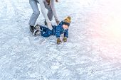 Young Mother Woman Raises Son Boy 4-6 Years Ice In Winter In City Park. The Concept Of First Lesson  poster