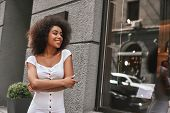 Young And Full Of Energy. Portrait Of Gorgeous Afro American Woman Standing Outdoors With Crossed Ar poster