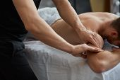 Young Handsome Man Enjoying A Back Massage. Professional Massage Therapist Is Treating A Male Patien poster