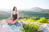 A Girl Is Sitting On Top Of A Mountain And Smiling. A Woman Admires The Beauty Of Nature. Travel To  poster