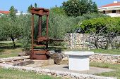 Large Rusted Metal Vintage Retro Olive Oil Press Machine Mounted On Concrete Foundation Next To Newl poster