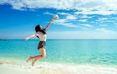 Happy Young Woman In Casual Style Fashion And Straw Hat Jumping At Sand Beach. Relaxing And Enjoy Ho poster