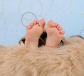 Extreme Close-up Of Child's Feet Over A Furry Blanket poster